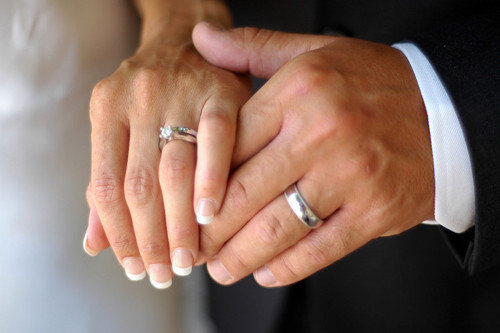 Holding Hands On Bible Wedding Ring